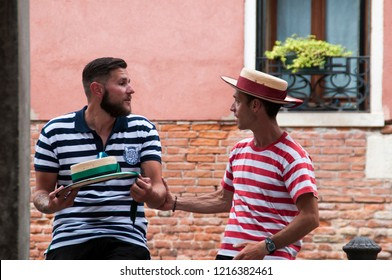 Venice, Italy - March 02 2017: Two young gondoliers talking with the typical uniform