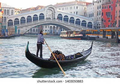 Venice, Italy - March 1, 2019: gondolier rowing a gondola on the Grand Canal in front of the Rialto Bridge