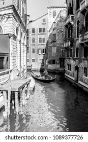 Venice, Italy - March 11, 2012: Typical Gondola with gondolier rowing along a narrow canal in Venice, black and white image.