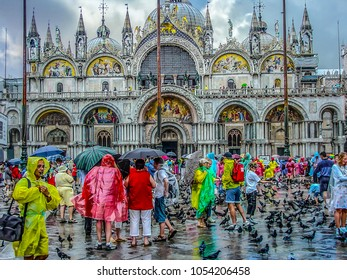 Venice, Italy - March 11 2015 - St Mark's Square in Venice Italy filled with pigeons and tourists wearing colorful raincoats and holding umbrellas on a rainy day in Spring in front of the cathedral