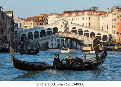 Venice, Italy - March 20, 2018: Venetian gondolier riding tourists on gondola at Grand Canal with Rialto bridge at background