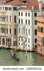 Venice, Italy - March 20, 2018: Venetian gondolier riding tourists on gondola at Grand Canal in Venice.