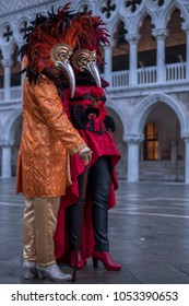 Venice, Italy, March 2018. Pair of costumed and masked carnival-goers standing in St Mark's Square during Venice Carnival (Carnivale di Venezia)