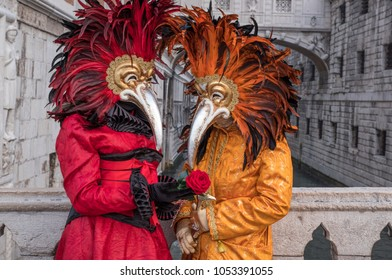 Venice, Italy, March 2018. Pair of costumed and masked carnival-goers standing in front of the Bridge of Sighs during Venice Carnival (Carnivale di Venezia)