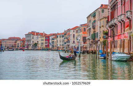 VENICE, ITALY - MARCH 21, 2015: Venetian gondolier punting gondola through green canal waters of Venice Italy