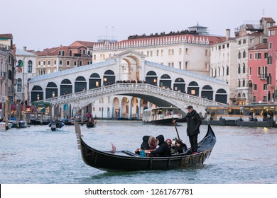 Venice, Italy - March 21, 2018: Venetian gondolier riding tourists on gondola at Grand Canal with Rialto bridge at background