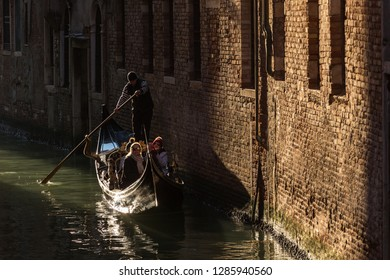 Venice, Italy - March 21, 2018: Venetian gondolier riding tourists on gondola through the side narrow canal in Venice.