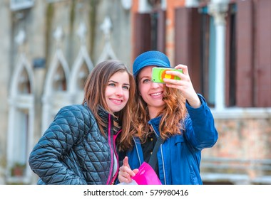 VENICE, ITALY - MARCH 22, 2015: Two happy famale young tourists take a selfie on the bridge.