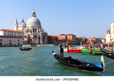 Venice, Italy - March 22, 2016: Gondoliers and Gondolas at Venice grand canal with the Basilica di Santa Maria della Salute in the background