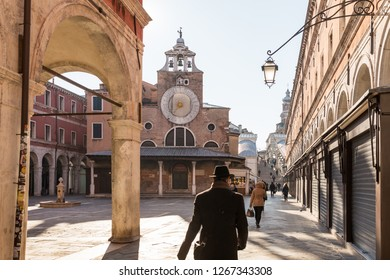 Venice, Italy - March 22, 2018: Unidentified people walk near the Church of San Giacomo di Rialto or Chiesa di San Giacomo di Rialto in Venice