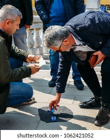 """Venice, Italy - March 28, 2018: Con artists perform """"Shell Game scam"""" to unsuspecting victims using matchsticks and small paper ball"""