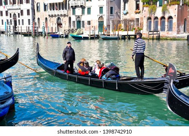 VENICE ITALY, MARCH 31 tourists on the gondola in a lagoon canal March 31 2019 Venice Italy