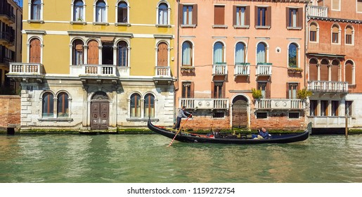 Venice, Italy, Marhc 27, 2017: A gondolier punting gondola with tourists through The Grand Canal in a sunny spring day. A gondolier is a Venetian boatman who propels a gondola.