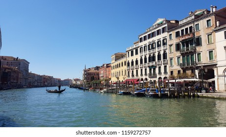 Venice, Italy, Marhc 27, 2017: A gondolier punting gondola through The Grand Canal in a sunny spring day. A gondolier is a Venetian boatman who propels a gondola.