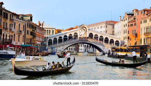 VENICE, ITALY - MAY 01 2011:Gondolas sail on the Grand Canal in Venice, Italy with the Rialto bridge in the background.About 30 million people visit the city each year.