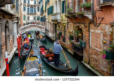 VENICE, ITALY - MAY 03, 2016:Girl watching from the balcony of Trattoria Sempione, the gondolas sailing through the venice canal Venice,Italy.