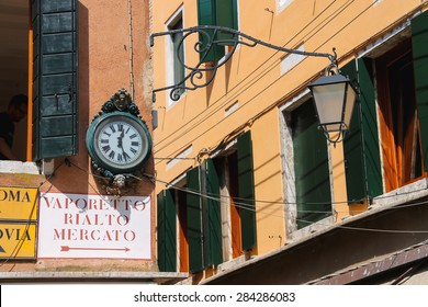 VENICE, ITALY - MAY 06, 2014: Clock and lantern hanging on a corner the house in Venice, Italy