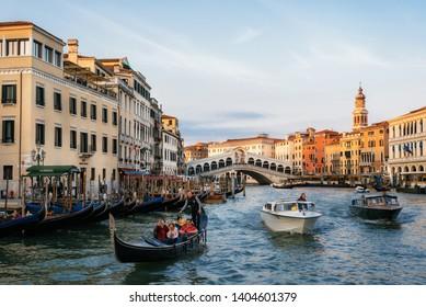 Venice, Italy - May 10, 2019: Rialto Bridge on Grand Canal with gondolas and speed boats taxi at sunset, Venice, Italy