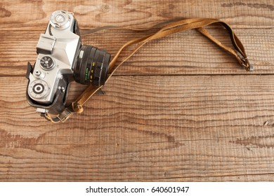 VENICE, ITALY - MAY 13, 2017: A Zenit EM is a vintage film camera made in URSS, lying over a dated wooden background