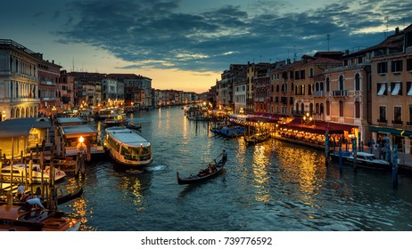 Venice, Italy - May 17, 2017: Grand Canal with gondola at night in Venice. It is one of the main travel attractions of Venice. Panoramic view and landscape of Venice.