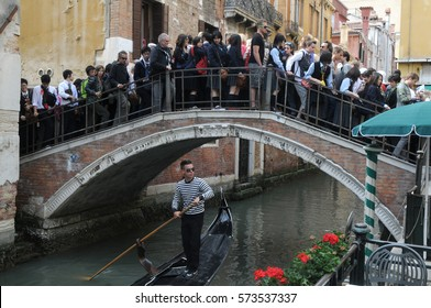 VENICE, ITALY - MAY 18, 2012: Tourists in the crowded the bridge in Venice.