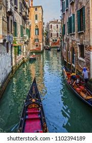 Venice, Italy - May 31, 2018: Gondolas in Venice canal, narrow street
