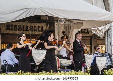 VENICE, ITALY - MAY 4: Tourists at San Marco square have a rest in one of many cafes with live music on May 4, 2012 in Venice, Italy. San Marco attracts more than 5 million visitors every year.