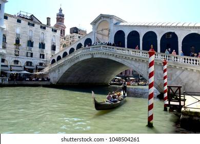 Venice, Italy, May 8th 2017: The Rialto Bridge, Venice, Italy with Gondola and Red & White Mooring Posts
