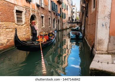 Venice, Italy - May 9, 2019: Venetian gondolier punts gondola through narrow canal waters of Venice Italy