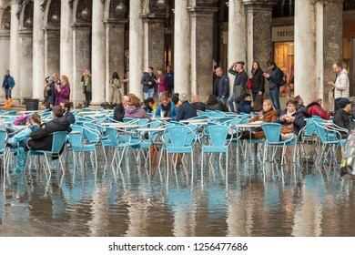 VENICE, ITALY - NOVEMBER 01, 2018: Scene of the flooded Piazza San Marco, with locals and tourists, in Venice, Veneto, Italy