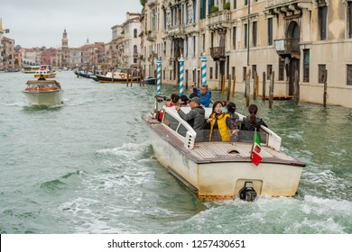VENICE, ITALY - NOVEMBER 01, 2018: Tourists on a water taxi in Venice taking photos and selfies.