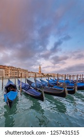 VENICE, ITALY - NOVEMBER 01, 2018:  Moored gondolas at sunset close to the Basilica di Santa Maria della Salute in Venice.