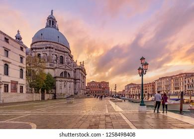VENICE, ITALY - NOVEMBER 01, 2018:  Tourists and street lamps at sunset close to the Basilica di Santa Maria della Salute in Venice.