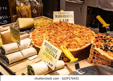 Venice, Italy - November 02 2018: Whole Italian cheese pizza pie in window display with vegetable/ vegetarian rolls. Fresh baked food on sale for lunch/ dinner meal. Traditional European dish cuisine.