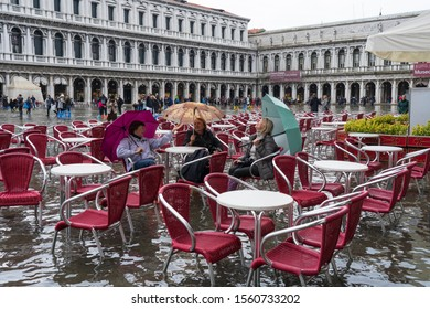 VENICE, ITALY - November 12, 2019: St. Marks Square (Piazza San Marco) during flood (acqua alta) in Venice, Italy. Venice high water. Tourists at St. Mark's Square during high water