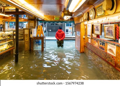 VENICE, ITALY - November 12, 2019: flood (acqua alta) in Venice, Italy. Venice high water. waiter in the middle of high water. Water in restaurant. Natural disaster