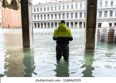 VENICE, ITALY - November 17, 2019: St. Marks Square (Piazza San Marco) during flood (acqua alta) in Venice, Italy. Venice high water. policeman in the water during a flood in Venice. Natural disaster
