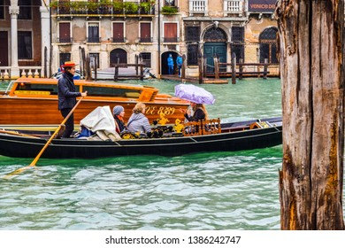 Venice, Italy - November 2, 2018: Female tourists on a famous gondola boat ride during rain in the city with Gondolier wearing straw hat, standing with rowing oar in hand.
