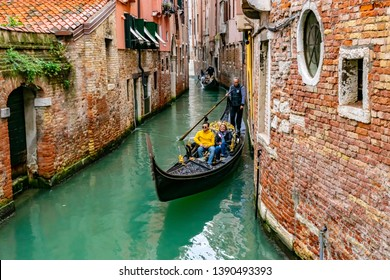 Venice, Italy - November 2, 2018: Smiling attractive Caucasian man and woman tourist couple riding in gondola. Gondolier standing on back navigating romantic scenic tour on water with single oar.