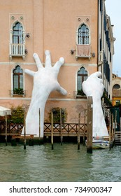 VENICE, ITALY - October 01, 2017: Lorenzo Quinn artwork Support with hands supporting Ca Sagredo Hotel and the Grand Canal at sunset , Venice, Veneto.