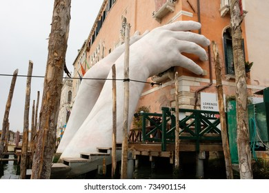 VENICE, ITALY - October 01, 2017: The sculpture 'Support' by Italian artist Lorenzo Quinn is seen in Venice. The artwork, featuring two hands holding up the Ca' Sagredo Hotel, is part of the Biennale