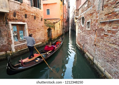 Venice, Italy - October 2018: A gondolier navigates his gondola with passengers across a narrow passageway in Venice's canals