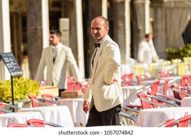VENICE, ITALY - OCTOBER 23, 2017: Waiters ready for service on a sunny morning in Piazza San Marco in Vencie Italy.
