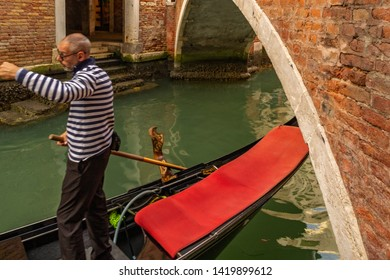 Venice, Italy - October 23, 2018, a gondolier carrying tourists through the narrow canals of the city of Venice. The concept of tourism and travel