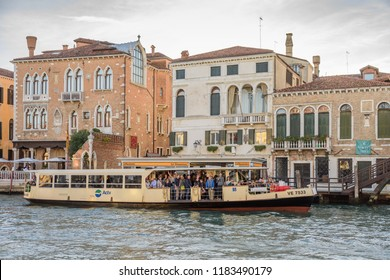 VENICE, ITALY - OCTOBER 24, 2018: A busy vaporetti canal bus leaving the Ca Rezzonico station on the grand canal in Vencie, Italy.