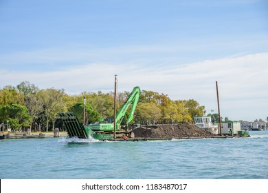 VENICE, ITALY - OCTOBER 25, 2018:  A dredger barge with a digger onboard near, Venice in Italy.