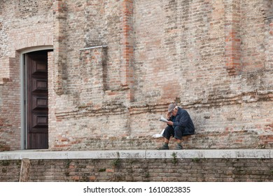 """Venice, Italy - October 27, 2017: Elderly man sitting at the back wall of  the art museum """"Magister Canova"""" at Fondamnta Misericordia in Venice reading newspaper."""