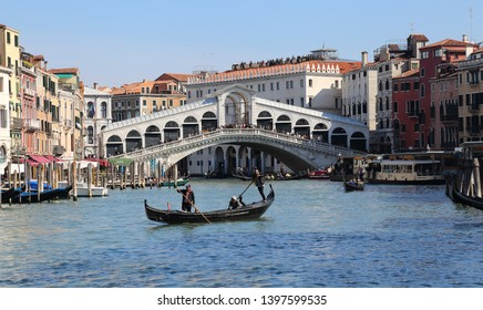 Venice, Italy - October 3, 2018: Gondolas with tourists and the Rialto bridge on the Grand Canal in Venice, Italy on October 3, 2018