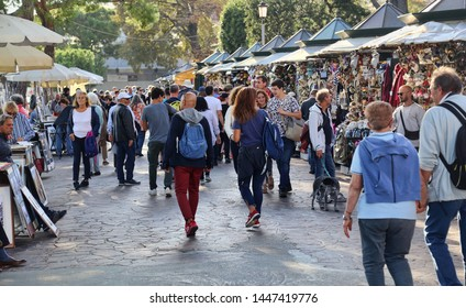 Venice, Italy - October 3 2018: Tourists walk along souvenir stalls on the waterfront in Venice, Italy on October 3, 2018