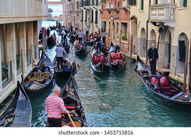 Venice, Italy - October 3 2018: Gondoliers and gondolas with tourists in a canal with hotels in Venice, Italy on October 3, 2018